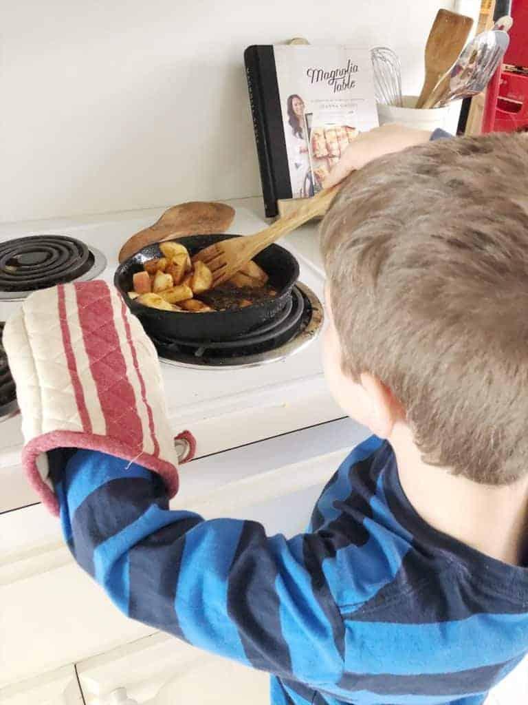 child stirring apples