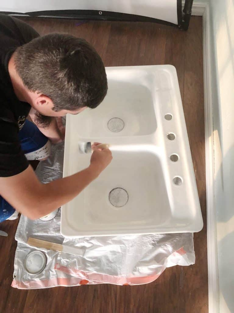 man painting kitchen sink
