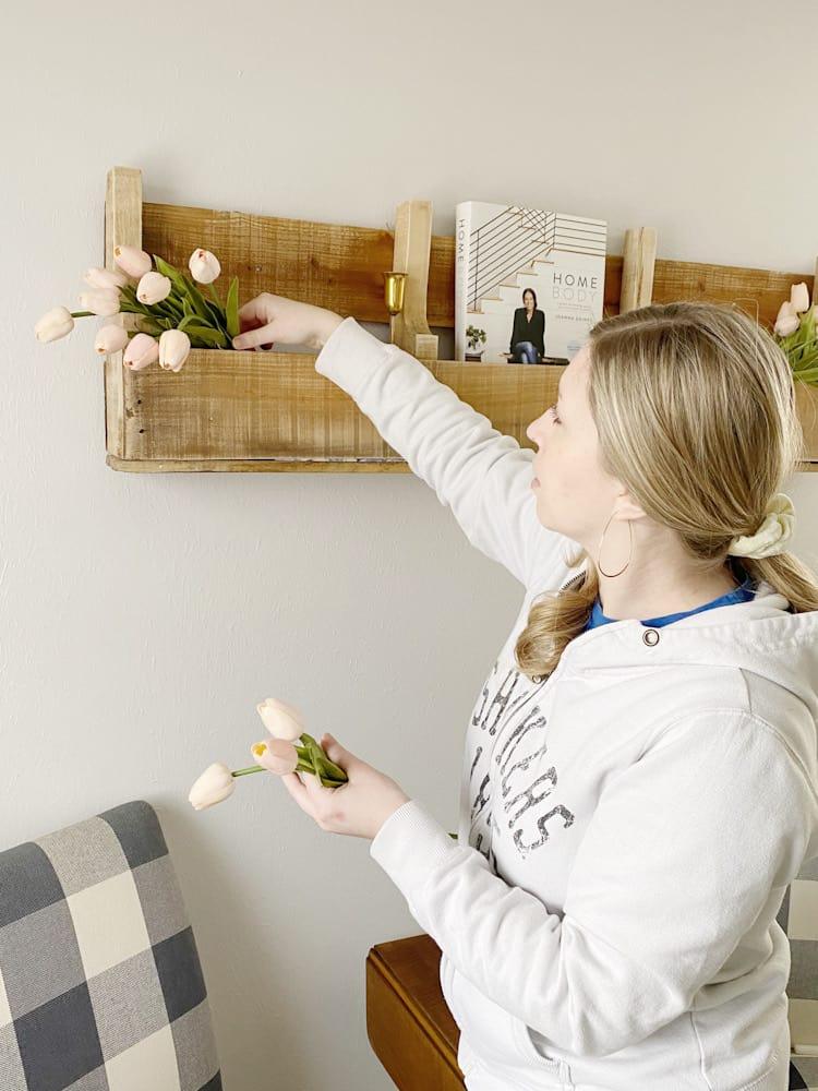 woman arranging tulips on shelf
