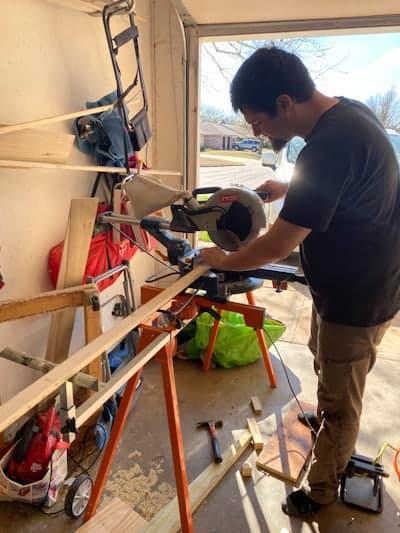 man cutting board with saw