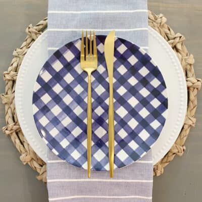 table setting with blue check plates and gold flatware