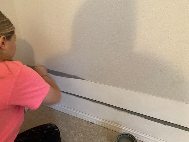 woman painting between shiplap boards