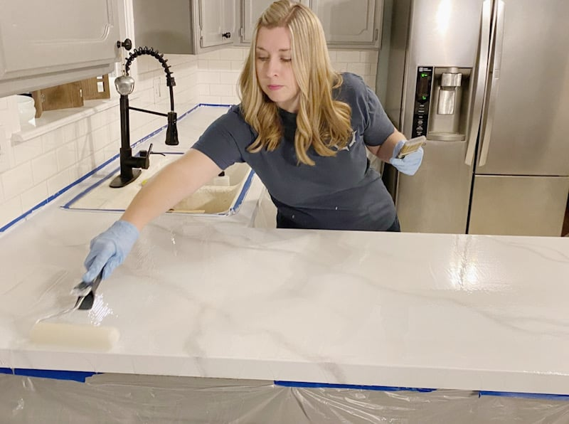 woman rolling topcoat on countertop